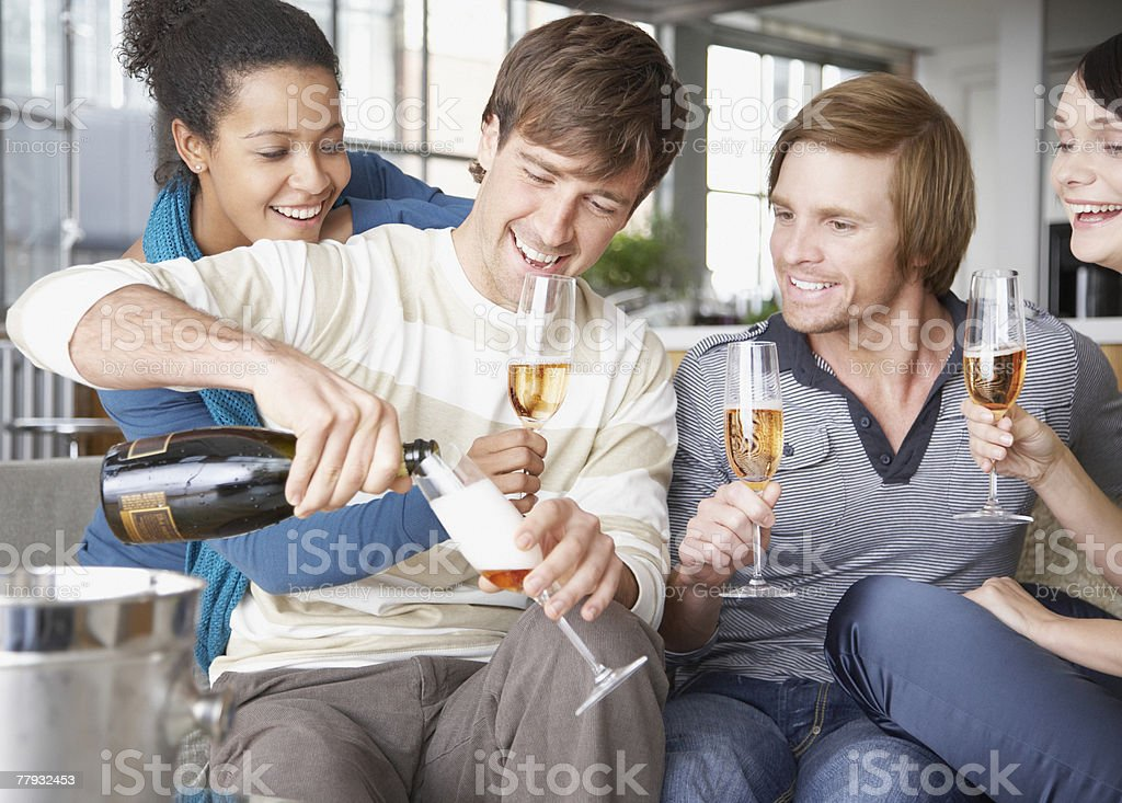 Four friends on sofa with champagne royalty-free stock photo