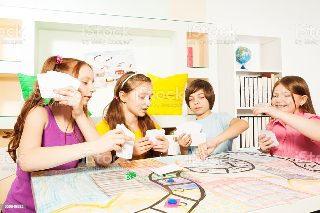 Four friends playing the tabletop game with cards stock photo