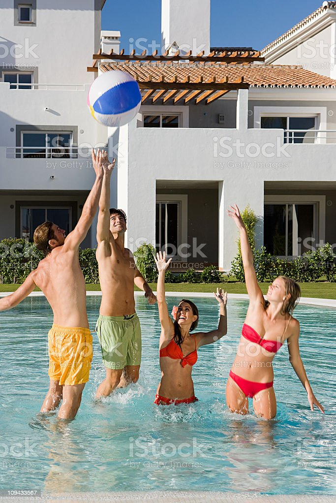 Four friends playing with beach ball in swimming pool royalty-free stock photo