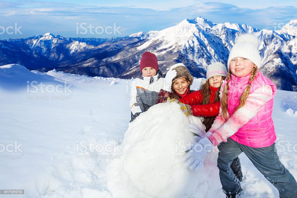 Four friends rolling the huge snowball on hill stock photo