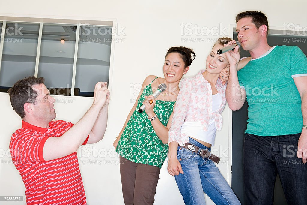 Four friends singing karaoke royalty-free 스톡 사진