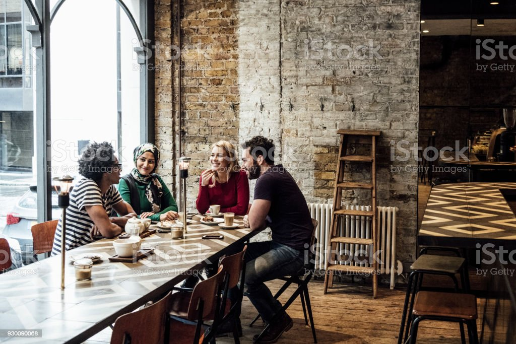 Four friends sitting at long table in cafe by window talking stock photo