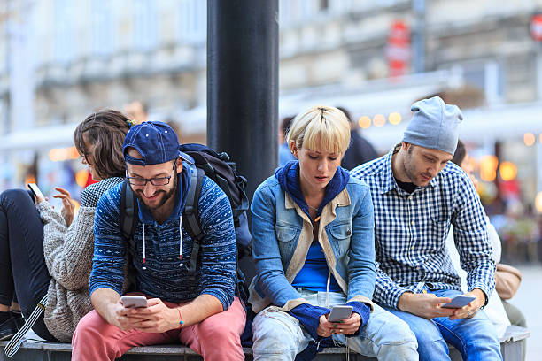four friends sitting on street and typing on smart phones - mobile game stock photos and pictures
