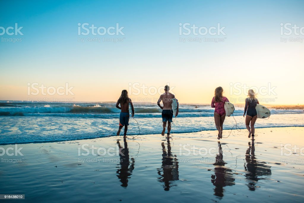 Four friends standing at the beach with surfboards stock photo
