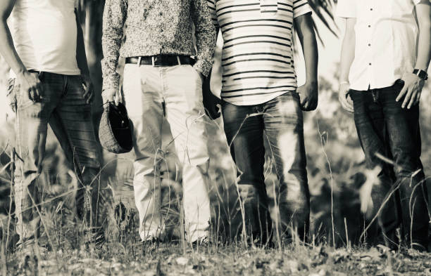 Four friends standing together around a place stock photo