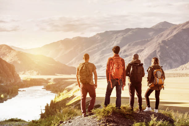 four friends sunset mountains travel concept - hiking stock photos and pictures