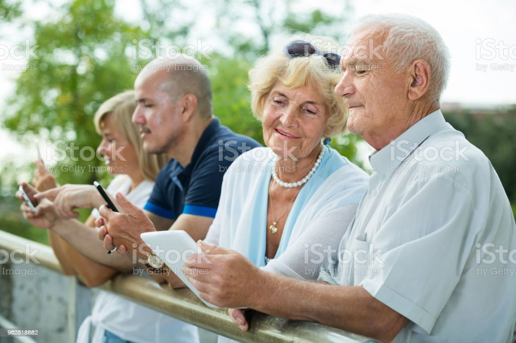 four  friends texting in phones in the park - Royalty-free 50-54 Years Stock Photo
