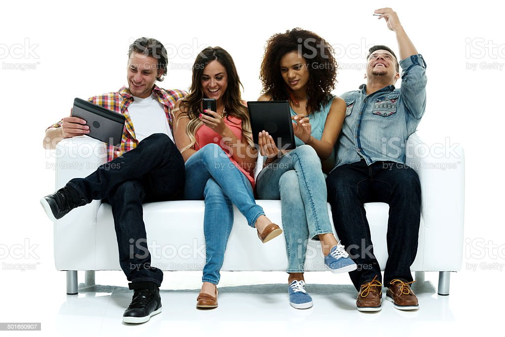 Four friends using mobile & tablet stock photo