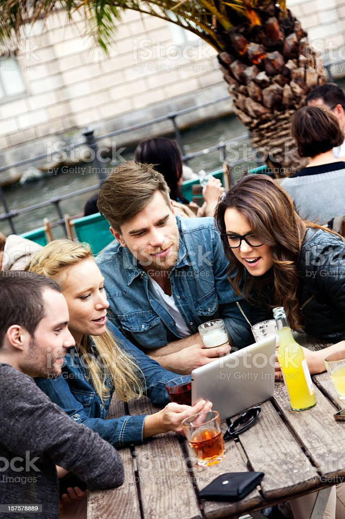 Four Friends with Tablet PC at Cafe royalty-free stock photo