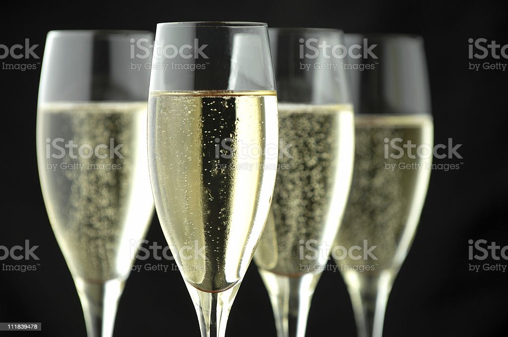 Four Full Champagne Flutes with Bubbles on Black royalty-free stock photo