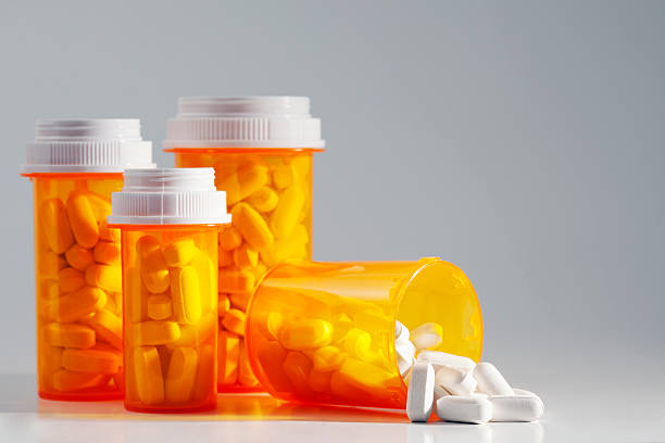 Four full prescription bottles with one spilling medication Prescription medication spilling from an open bottle. This macro shot shows caplets or pills in the opening of a medicine bottle with other standing bottles in the background. The photo includes open space for your copy. generic drug stock pictures, royalty-free photos & images