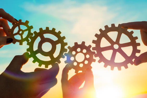 four gears in hands on a sunset background. four gears in hands on a sunset background. teamwork. order stock pictures, royalty-free photos & images