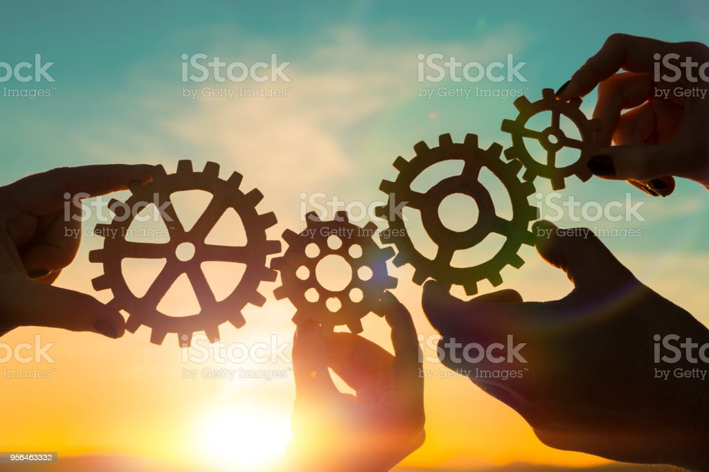four gears in hands four gears in hands on a sunset background. teamwork. Agreement Stock Photo
