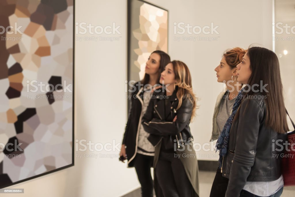 Four girl friends looking at modern painting in art gallery stock photo