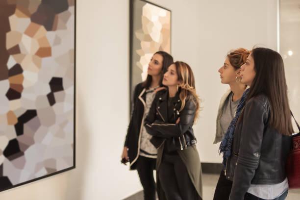vier freundinnen blick auf moderne malerei in kunstgalerie - gemäldegalerie stock-fotos und bilder