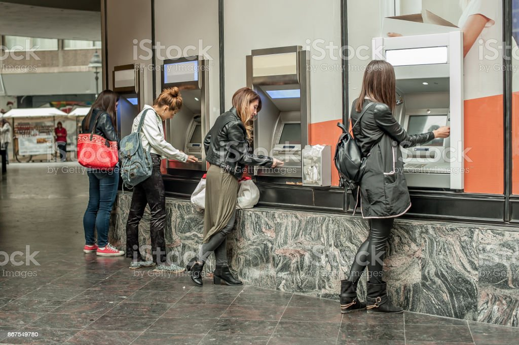 Four girl friends withdrawing money from credit card at ATM stock photo