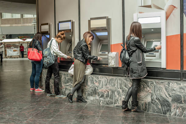 four girl friends withdrawing money from credit card at atm - banks and atms stock pictures, royalty-free photos & images