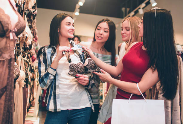 Four girls are in underwear shop. Brunette girl is holding bra while her friends are giving advises to her. They are helping her. Four girls are in underwear shop. Brunette girl is holding bra while her friends are giving advises to her. They are helping her bra stock pictures, royalty-free photos & images