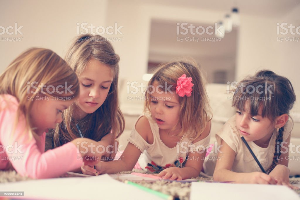 Four girls lying on the floor. stock photo