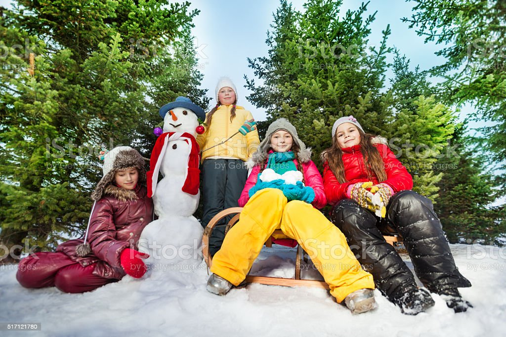 Four girls made funny snowman at the forest stock photo
