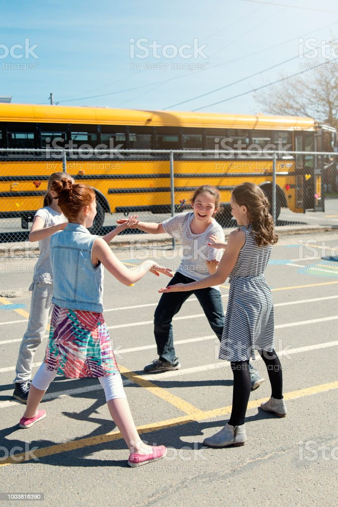 Four girls playing hand games in school playground at recess.. stock photo