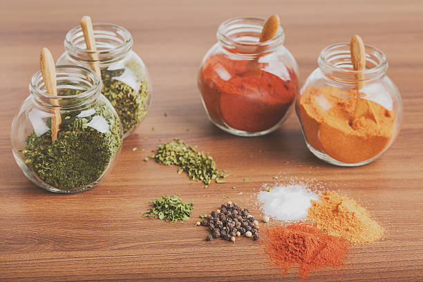 four glass jar with spices and spices heap - peperoni stiche stock-fotos und bilder