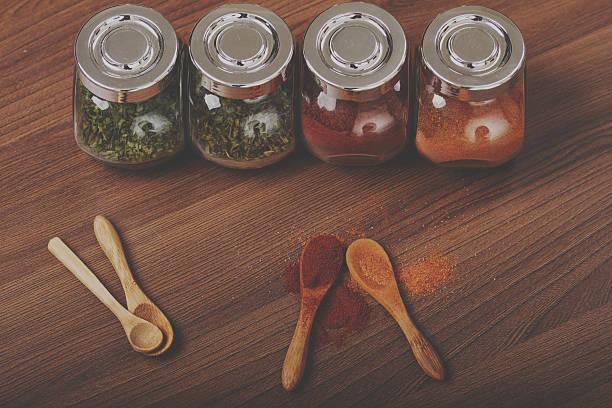 four glass jar with spices - peperoni stiche stock-fotos und bilder
