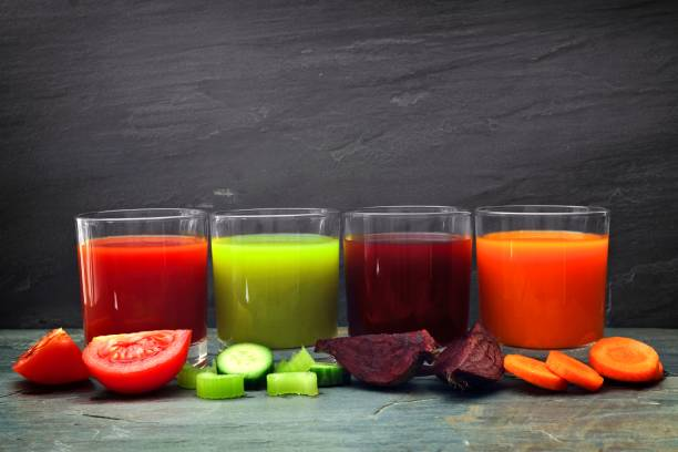 Four glasses of healthy vegetable juice over slate Four glasses of healthy vegetable juice with scattered vegetables and a dark slate background vegetable juice stock pictures, royalty-free photos & images