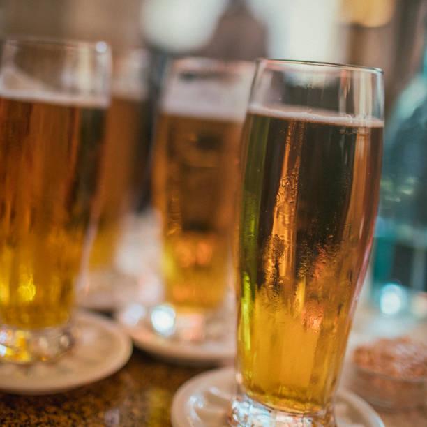quatro copos de cerveja pilsner em uma tabela, como tiro em praga. - praga boémia - fotografias e filmes do acervo