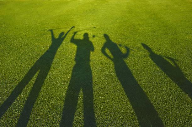 Four golfers silhouette on grass stock photo