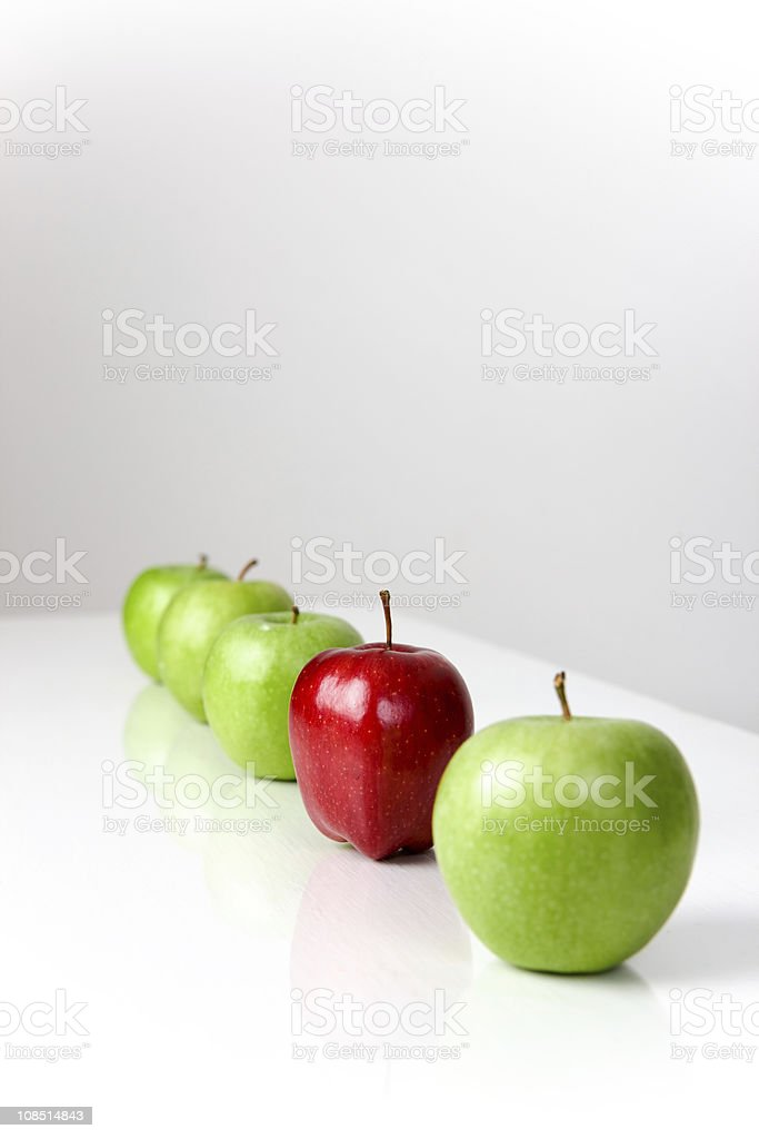 Four green apples and one red apple placed in a row royalty-free stock photo