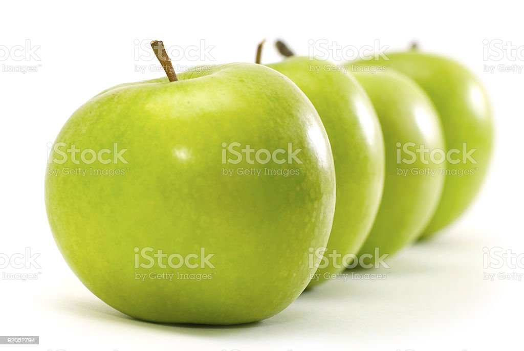 Four green apples in a straight line on a white background stock photo