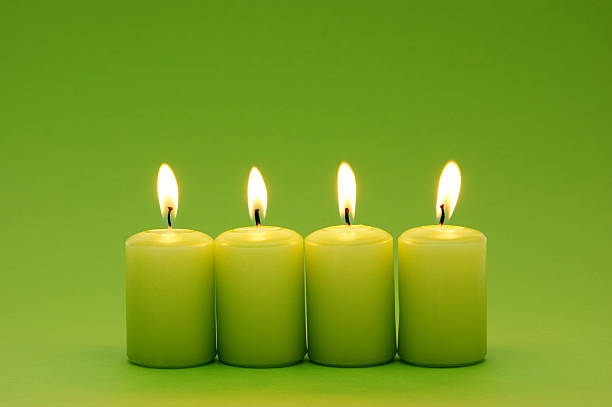 Four green candles in a row lit up stock photo