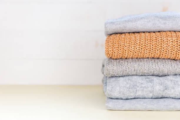 Four grey and one yellow folded knitted jumpers laying on yellow pastel surface. Minimal concept. Autumn, fall, winter fashion. stock photo