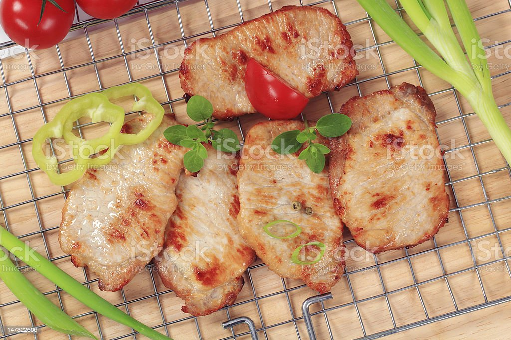 Four grilled pork steaks on a  grill grid royalty-free stock photo