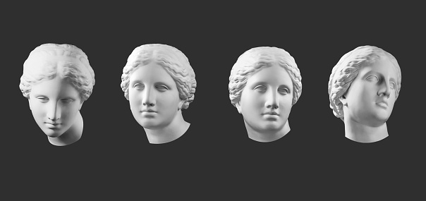 Four white gypsum copy of ancient statue of Venus de Milo head for artists isolated on a black background. Plaster sculpture of woman face.