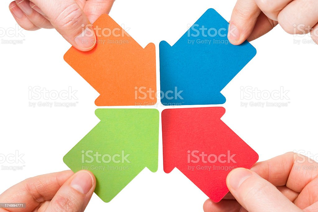 Four handheld colourful arrows point to the centre royalty-free stock photo