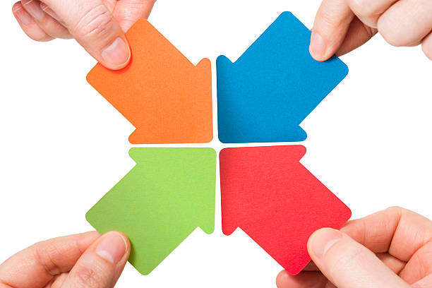 Four handheld colourful arrows point to the centre stock photo