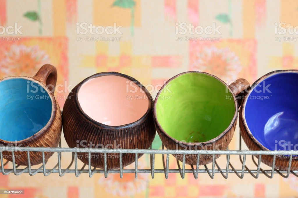Four handmade crafts ceramic clay cup mug different colors on stand for dishes. Kitchenware. Homeliness. Comfort in home. Beautiful tableware. stock photo