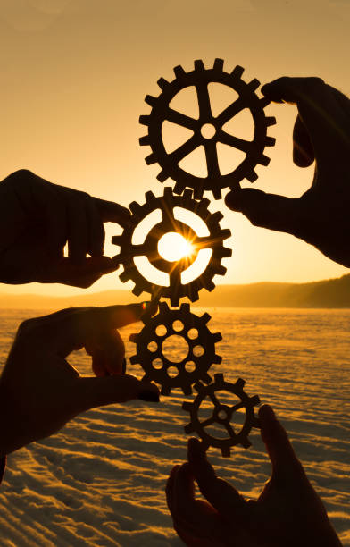 four hands are holding the gears against the sunset. stock photo