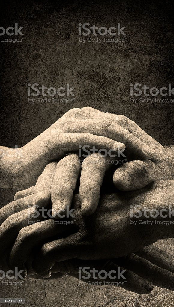 Four Hands Clasped Together in Unity, Black and White Textured royalty-free stock photo