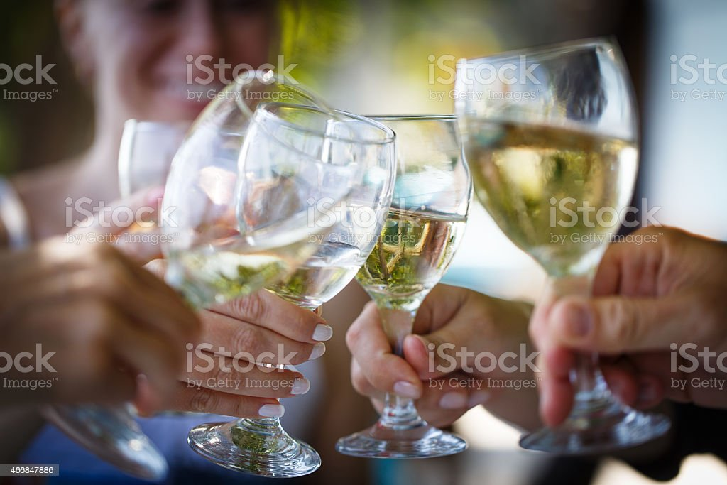 Four hands making cheers with glasses stock photo