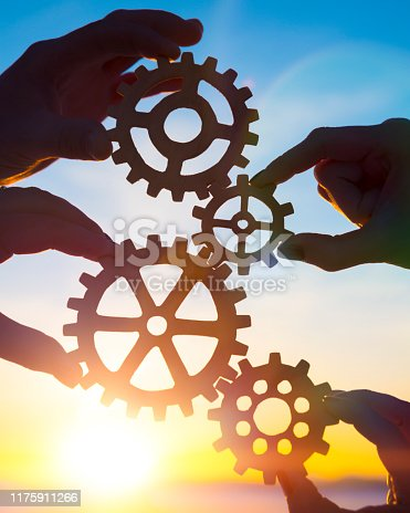 Four hands of businessmen collect gear from the gears of the details of puzzles. against the background of sunlight. The concept of a business idea. Teamwork. strategy, cooperation. Close-up