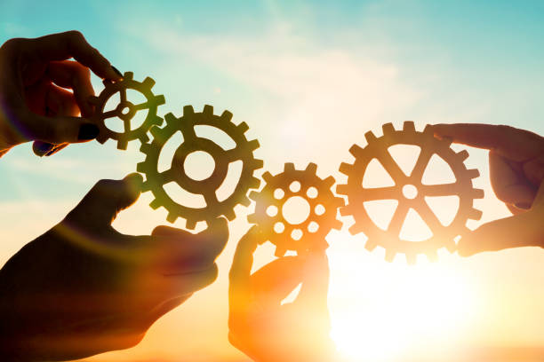 Four hands of businessmen collect gear from the gears of the details of puzzles. against the sunset. stock photo