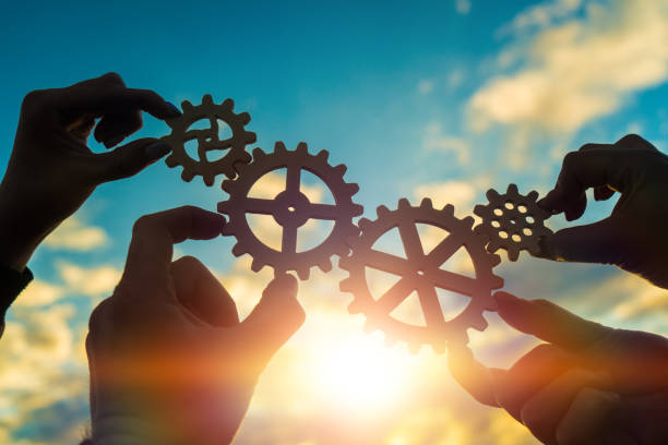Four hands of businessmen connect gears to a puzzle on a background of sunset. Business concept idea stock photo