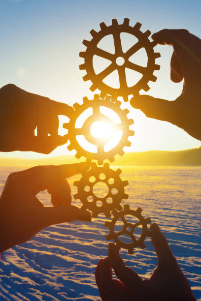 Four hands of businessmen holding gears folded into a puzzle mechanism at sunset. stock photo