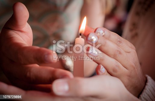 istock four hands of young people protecting fragile candle light fire as a metaphor of care and protection during religious ceremony 1079725694