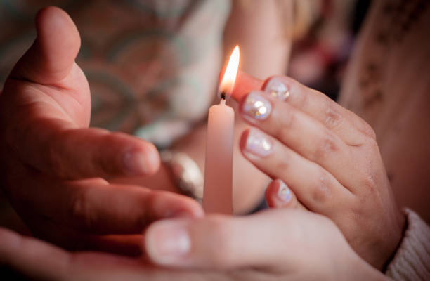 four hands of young people protecting fragile candle light fire as a metaphor of care and protection during religious ceremony stock photo