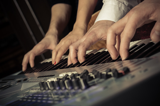 Four hands on the keys of the synthesizer shot with a shallow depth of field