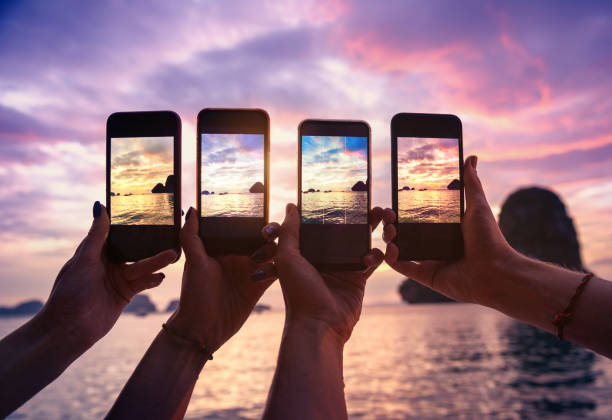 Four hands with mobile phones taking photo Closeup photo of four hands with mobile phones taking photo of beautiful sunset over sea bay four people stock pictures, royalty-free photos & images